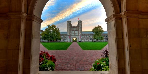 colorful sky above Brookings hall, as seen through a stone archway across the quad