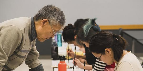 Professor Fred Wu watches students practicing calligraphy
